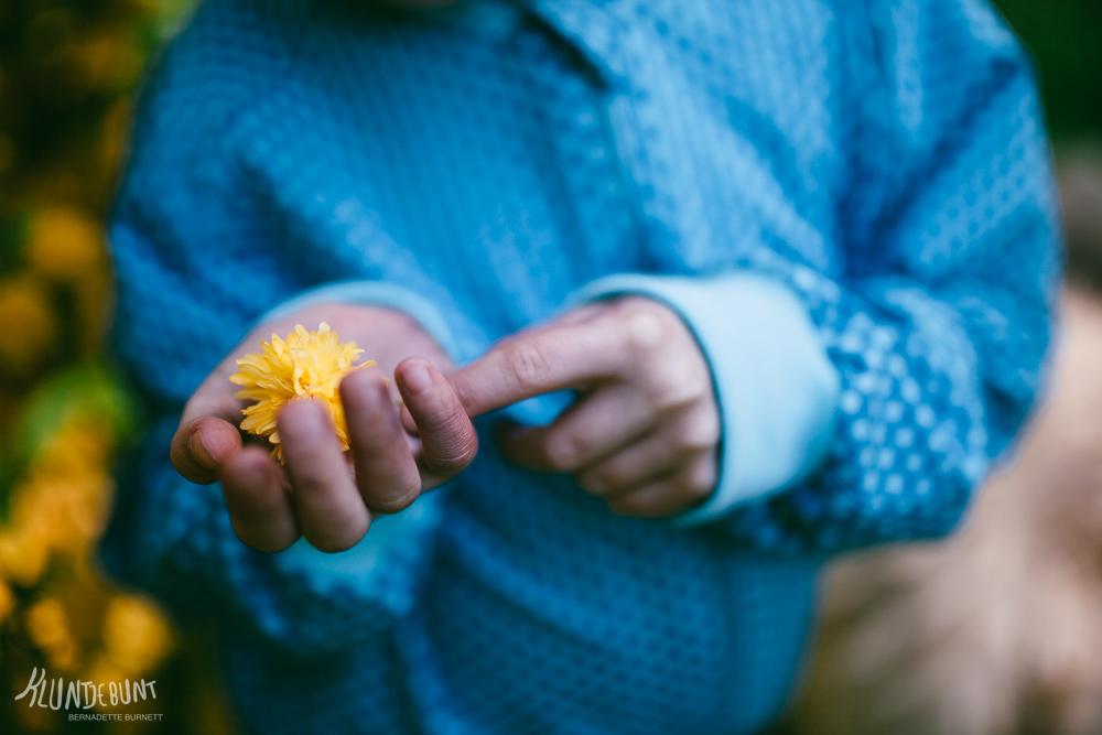 Kind hält Blüte in den Händen und trägt Bomberjacke