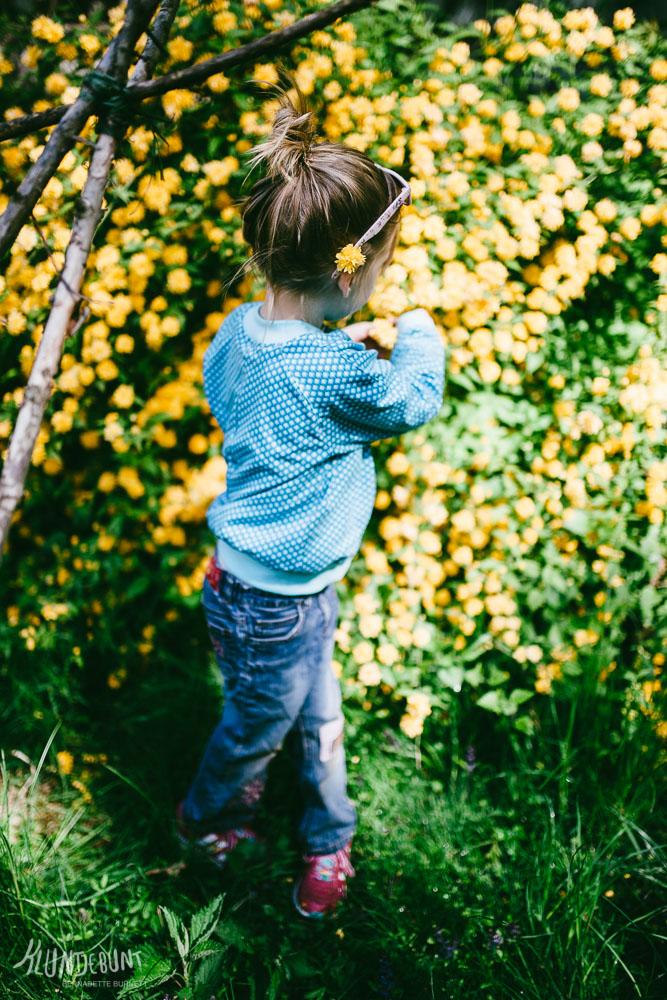 Kind im Garten vor einem blühenden Busch mit selbstgenähter Jacke und Sonnenbrille