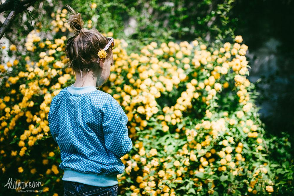 Kind mit Sonnenbrille mit dem Rücken zugewandt vor einem blühenden Busch im Garten