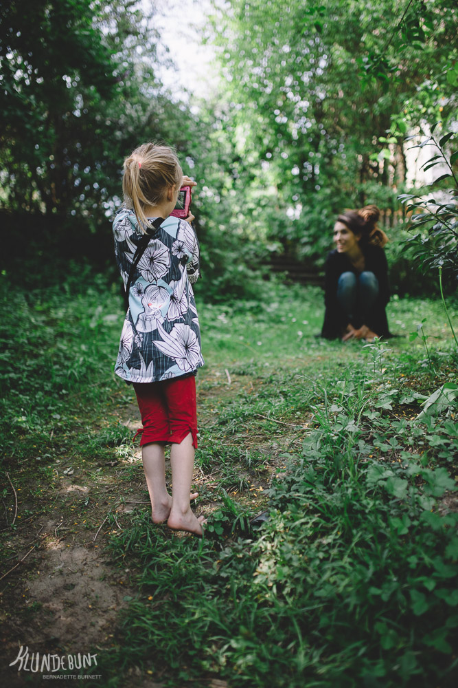 Kind fotografiert junge Frau auf Wiese