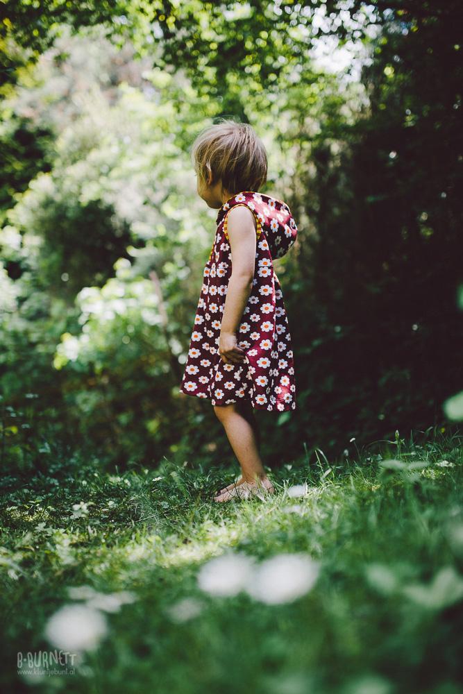 Kleinkind in grüner Wiese mit buntem BIO Kapuzenkleid