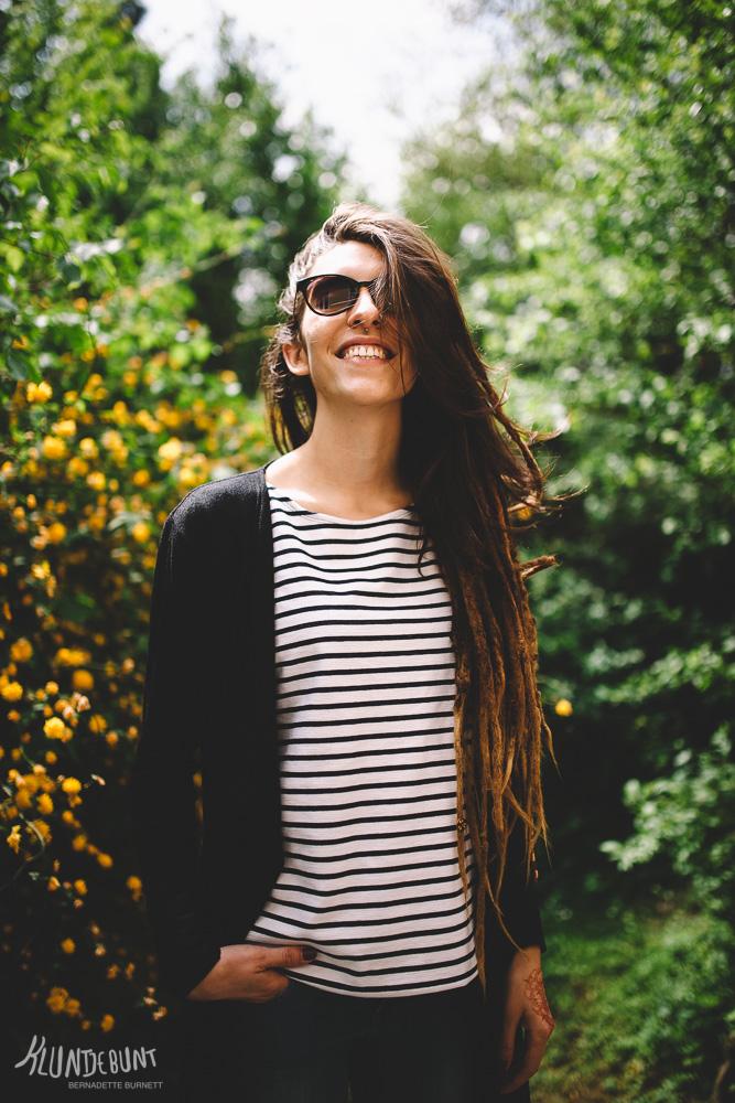 Junge Frau mit Sonnenbrille grinst in die Kamera