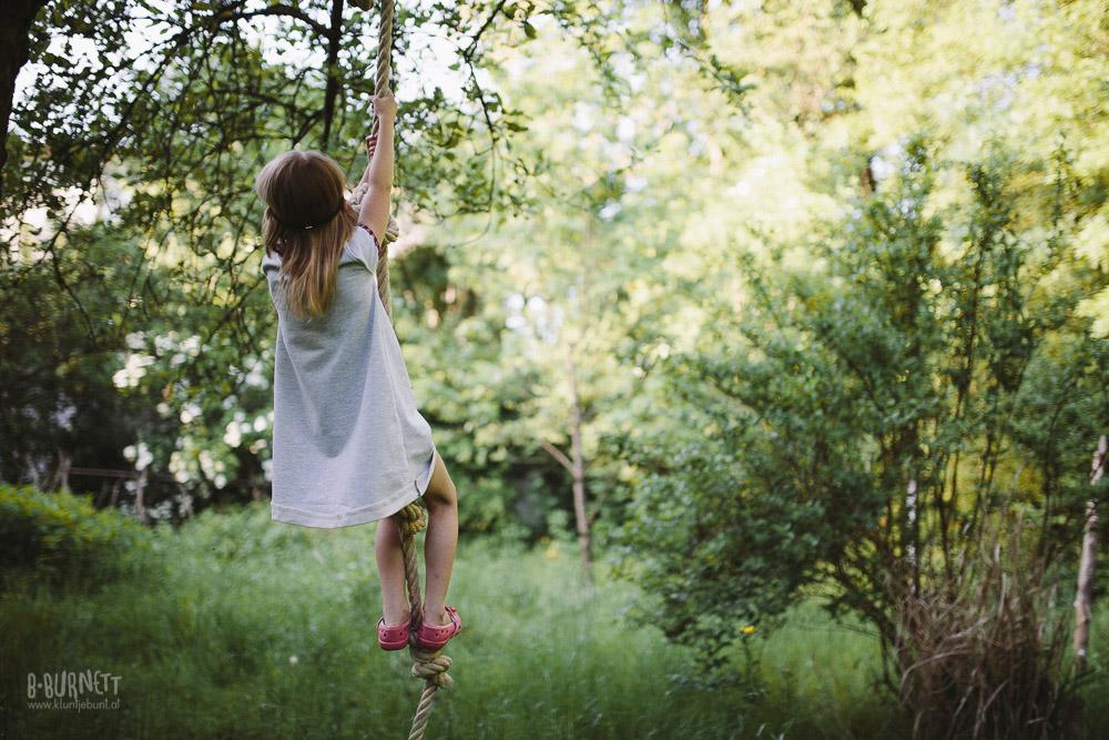 Mädchen an Tau im Garten in Kinderkleid