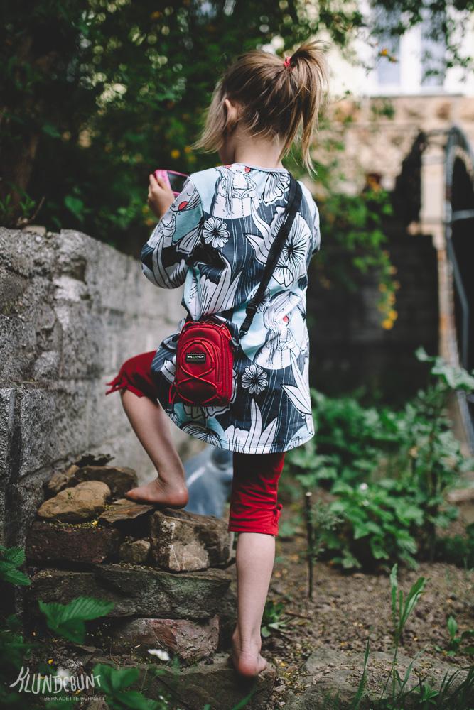 Kind in selbstgenähter Tunika mit Kamera kniet klettert auf einen kleinen Stein-Haufen