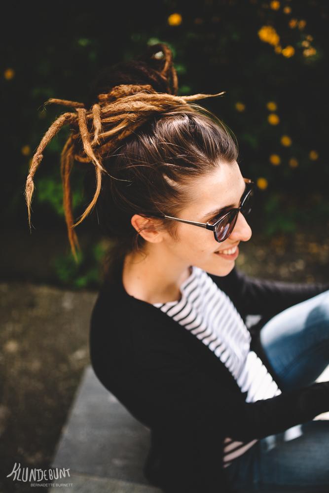 Junge Frau mit Dreadlocks in moderner Kleidung lächelt